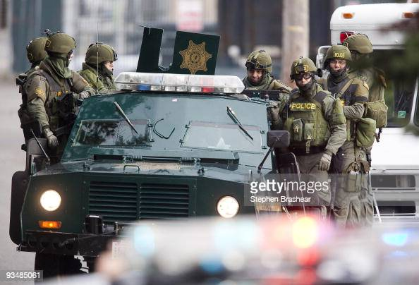 SWAT team members ride on a armored vehicle while searching for a suspect November 29 2009 near Lakewood Washington A gunman shot and killed four...