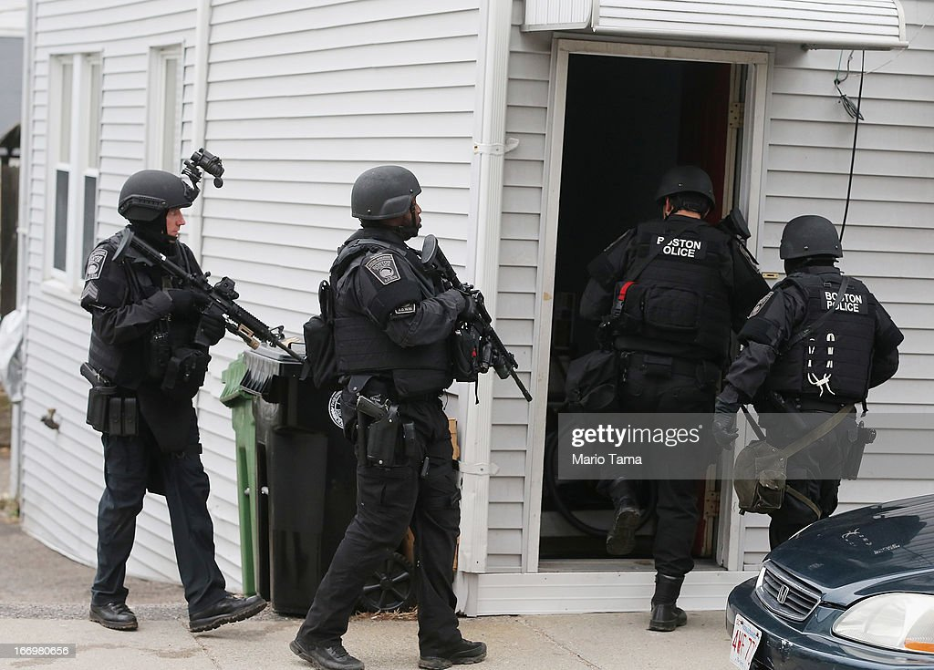 SWAT team members search for one remaining suspect at a residential building on April 19, 2013 in Watertown, Massachusetts. Earlier, a Massachusetts Institute of Technology campus police officer was shot and killed at the school's campus in Cambridge. A short time later, police reported exchanging gunfire with alleged carjackers in Watertown, a city near Cambridge. According to reports, one suspect has been killed during a car chase and the police are seeking another - believed to be the same person (known as Suspect Two) wanted in connection with the deadly bombing at the Boston Marathon earlier this week. Police have confirmed that the dead assailant is Suspect One from the recently released marathon bombing photographs.