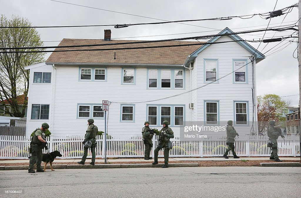 SWAT team members stand in front of a house while looking for 19-year-old bombing suspect Dzhokhar A. Tsarnaev, during a door-to-door search on April 19, 2013 in Watertown, Massachusetts. After a car chase and shoot out with police, one suspect in the Boston Marathon bombing, Tamerlan Tsarnaev, 26, was shot and killed by police early morning April 19, and a manhunt is underway for his brother and second suspect, 19-year-old Dzhokhar A. Tsarnaev. The two men are suspects in the bombings at the Boston Marathon on April 15, that killed three people and wounded at least 170.