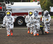 In any urban area the fire departments and emergency response teams will conduct disaster preparedness drills. These HAZMAT team members are suited up with a protective suit to protect them from hazar