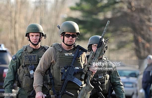 FBI SWAT team members walk along Dickinson Drive near Sandy Hook Elementary School in Newtown Connecticut Friday December 14 2012 Twentyseven people...