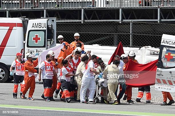 Team Moto2 Spanish rider Luis Salom is evacuated by medical personnel after resulting injured in an accident at the Catalunya racetrack in Montmelo...