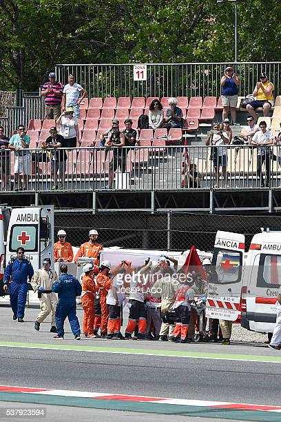 SAG Team Moto2's Spanish rider Luis Salom is evacuated by medical personnel after resulting injured in an accident at the Catalunya racetrack in...
