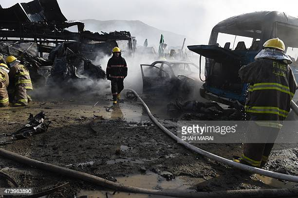 A team of Afghan firefighters work to contain fires at the site of a suspected suicide bomber that struck a parking lot as a body of a victim lays...