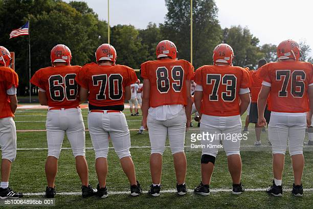 Team of American football players including teenagers (15-17) in row, rear view