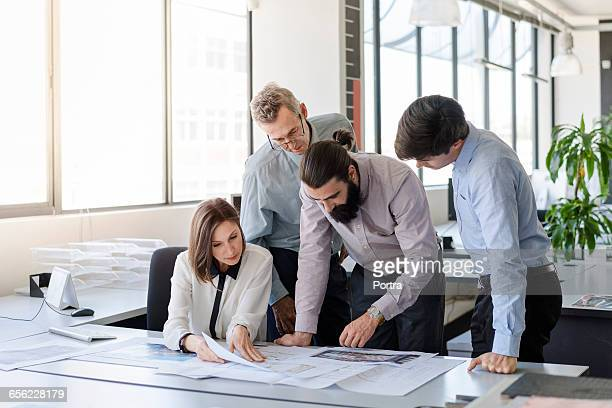 Team of architects examining blueprints in office