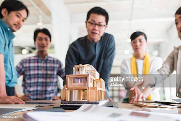 Team of architects looking at a 3D model