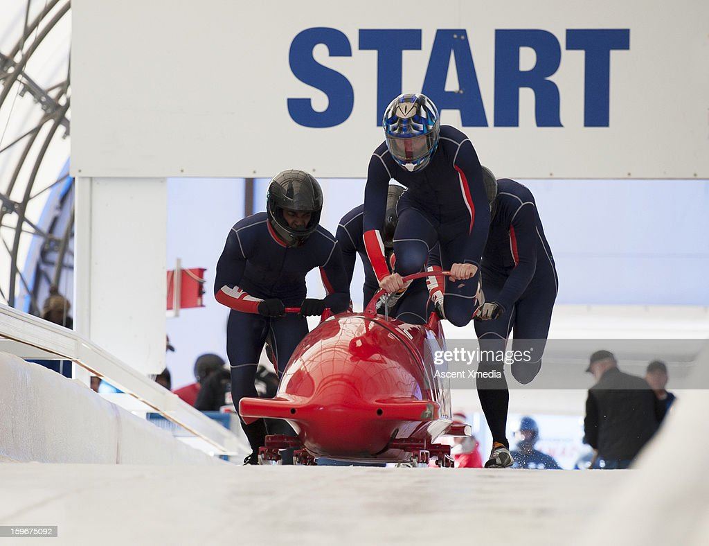 Team of bobsledders push bobsled out of start gate : Stock Photo