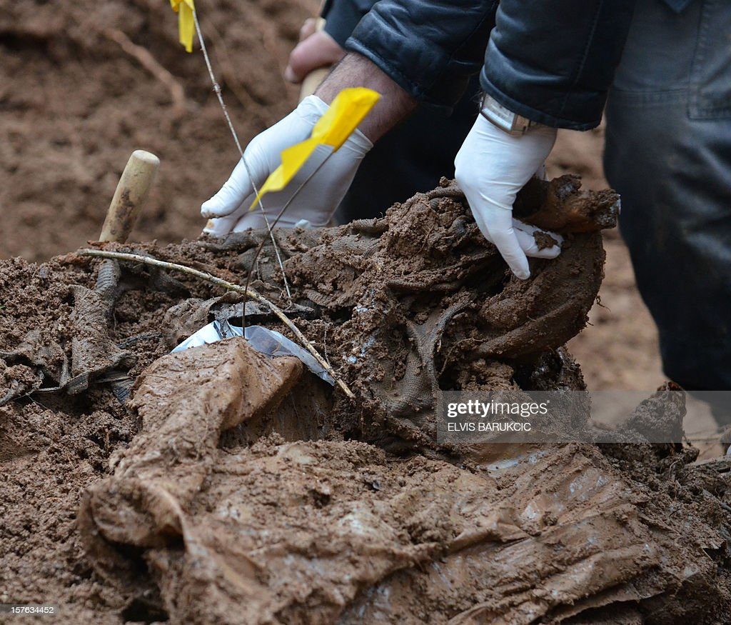 A team of Bosnian forensic experts inspect material evidence found while excavating a potential mass grave site in the village of Misevici, a western suburb of Sarajevo, on December 5, 2012. The forensic team reacted upon an instruction by the Sarajevo District Prosecutor. Only two complete body remains were retrieved on Wednesday, more are expected to be found as the excavation continues. Bodies are believed to belong to Bosnian Muslims killed in the spring of 1992, by Bosnian Serb forces.