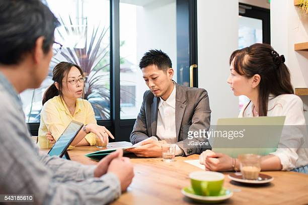 Team of business men and women around a table