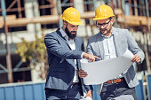 Two engineer have consulting meeting at construction site.Two construction worker working at construction site.