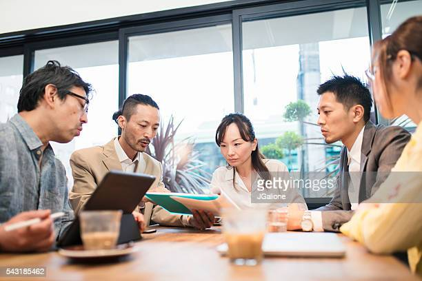 Team of businessmen and women around a table