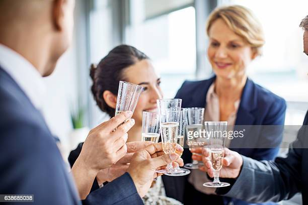 Team of businesspeople toasting champagne