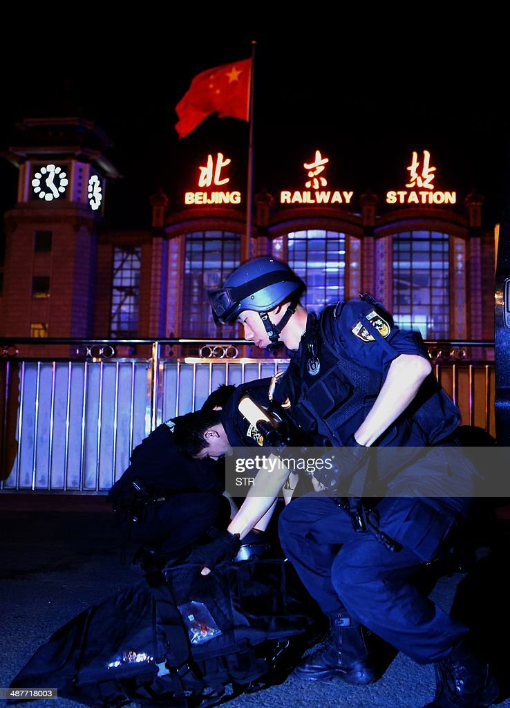 A team of Chinese special police prepare their weapons during a drill at the railway station in Beijing on the early hours of May 2, 2014. Chinese President Xi Jinping ordered a crackdown after a stabbing spree and explosion at a railway station in the restive Muslim-majority region of Xinjiang left two attackers and a civilian dead and 79 wounded, state media said. CHINA