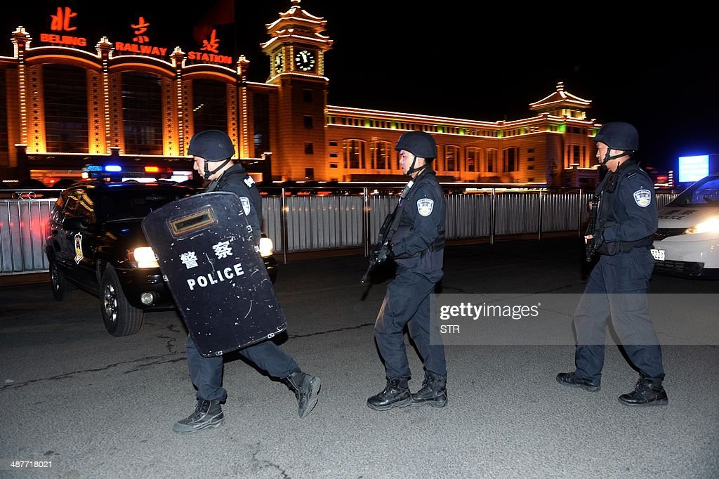 A team of Chinese special police take up position during a drill outside the railway station in Beijing on the early hours of May 2, 2014. Chinese President Xi Jinping ordered a crackdown after a stabbing spree and explosion at a railway station in the restive Muslim-majority region of Xinjiang left two attackers and a civilian dead and 79 wounded, state media said. CHINA OUT AFP PHOTO