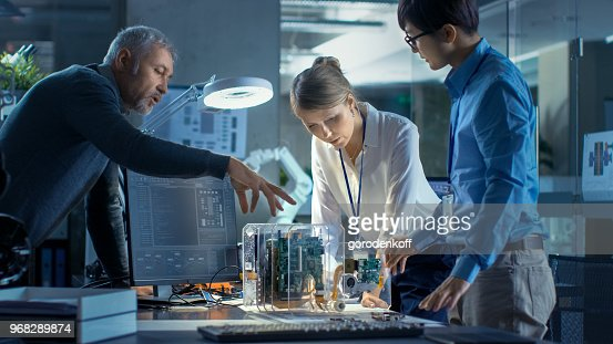 Team of Computer Engineers Lean on the Desk and Choose Printed Circuit Boards to Work with, Computer Shows Programming in Progress. In The Background Technologically Advanced Scientific Research Center. : Stock Photo
