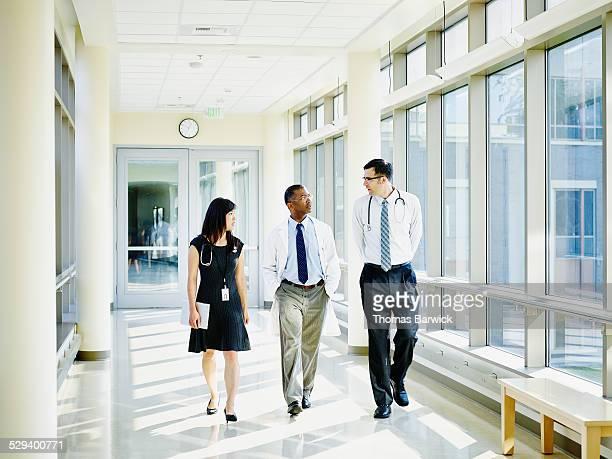 Team of doctors walking through hospital corridor