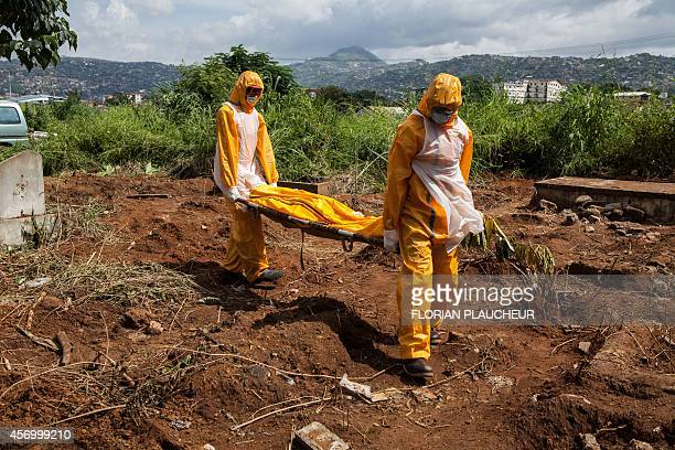 A team of funeral agents specialised in the burial of victims of the Ebola virus carry a body prior to put it in a grave at the Fing Tom cemetery in...