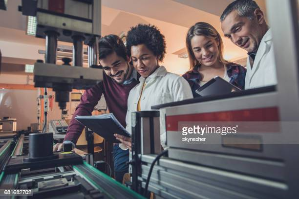 Team of happy engineers analyzing data of a manufacturing machine.