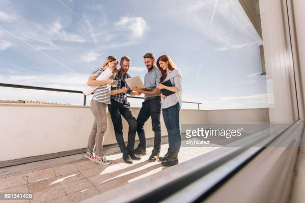 Team of happy freelance workers standing on a terrace and working on a computer.