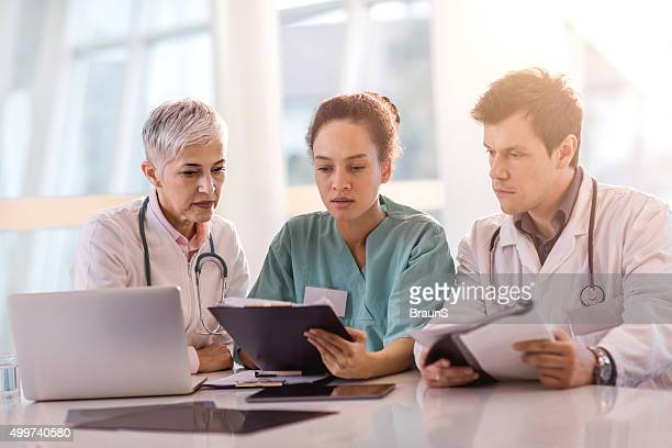 Team of healthcare workers reading medical documents together.