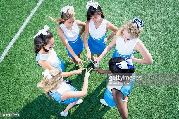 Team of High School Cheerleaders Huddled on Sidelines