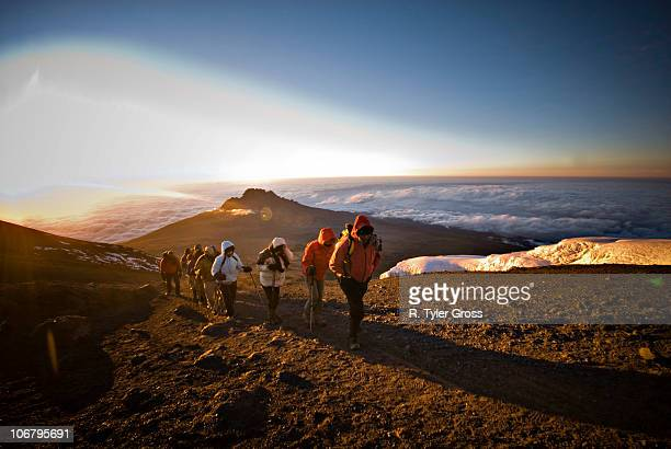 A team of hikers approach the summit of Mt. Kilimanjaro at sunrise after trekking six hours through the night.