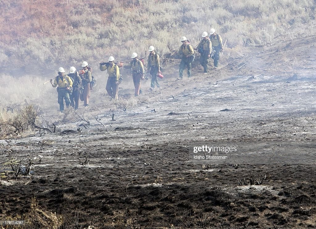 A team of hotshots walk along a fire line near homes on Croy Road and the Rotorun ski hill west of Hailey, Idaho, Saturday, August 17, 2013. The Beaver Creek fire moved through the area in the early hours Saturday morning.
