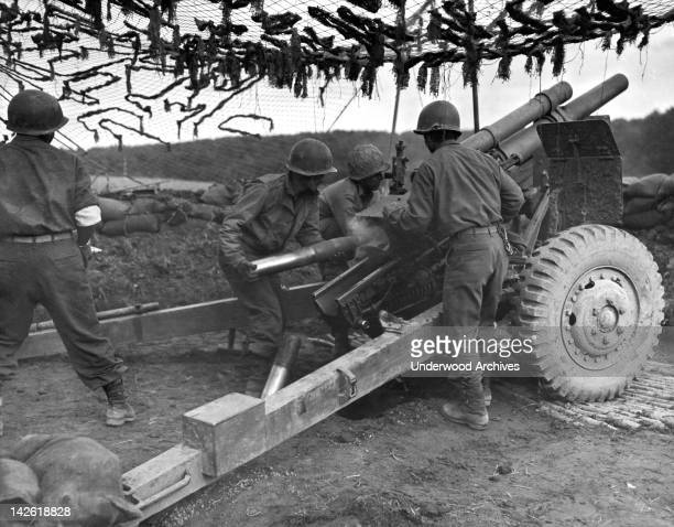 A team of JapaneseAmerican GI's firing 105 mm shells at Germans in support of an infantry attack France October 18 1944