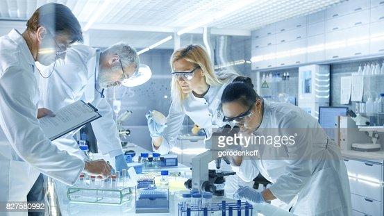 Team der medizinischen Forschungswissenschaftler arbeiten an eine neuen Generation-Krankheit zu heilen. Sie verwenden Mikroskop, Reagenzgläser, Mikropipette und schreiben Sie Analyseergebnisse. Labor sieht beschäftigt, hell und Modern. : Stock-Foto