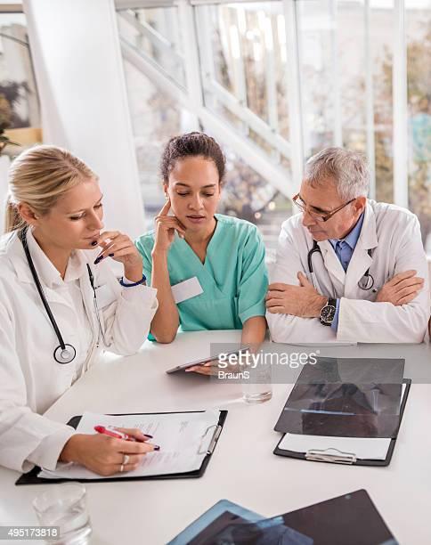 Team of medical workers working on digital tablet.