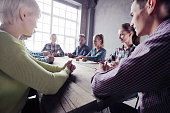 Team of people in casual clother working together sitting around wooden table and pointing at center, startup concept