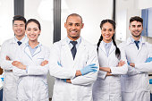 Team of young professional doctors standing together in laboratory, posing with arms crossed