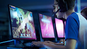 Team of Professional eSport Gamers Playing in Competitive  MMORPG/ Strategy Video Game on a Cyber Games Tournament. They Talk to Each other into Microphones. Arena Looks Cool with Neon Lights.