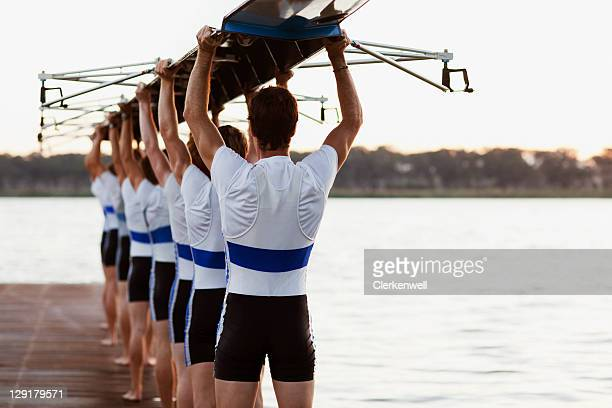 Team of rowers carrying a crew canoe over heads