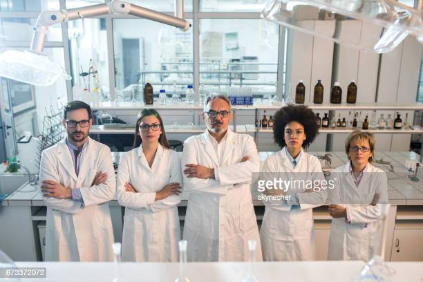 Team of scientist with their arms crossed in a laboratory.