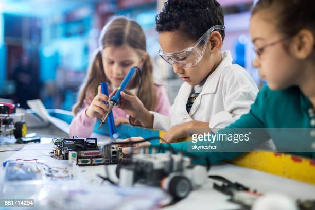 Team of small engineers working on a computer part in laboratory.