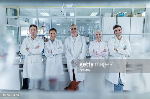 Team of smiling chemists with crossed arms in a laboratory.