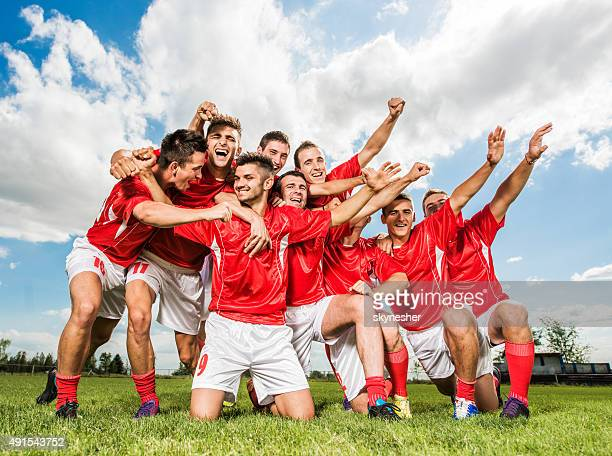 Team of soccer players celebrating on playing field.