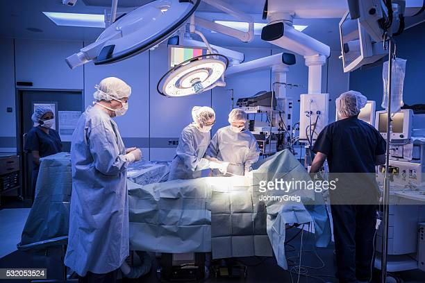 Team of surgeons operating on patient in hospital