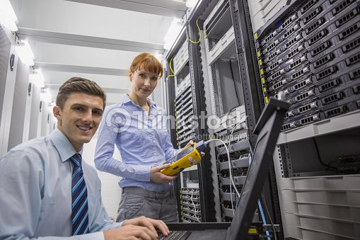 Team of technicians using digital cable analyser on servers : Stock Photo