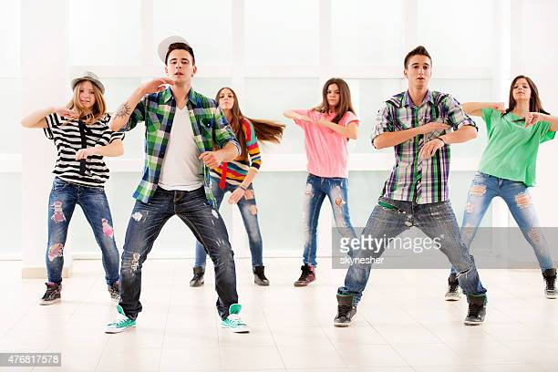 Team of teenage dancers exercising hip hop dance.