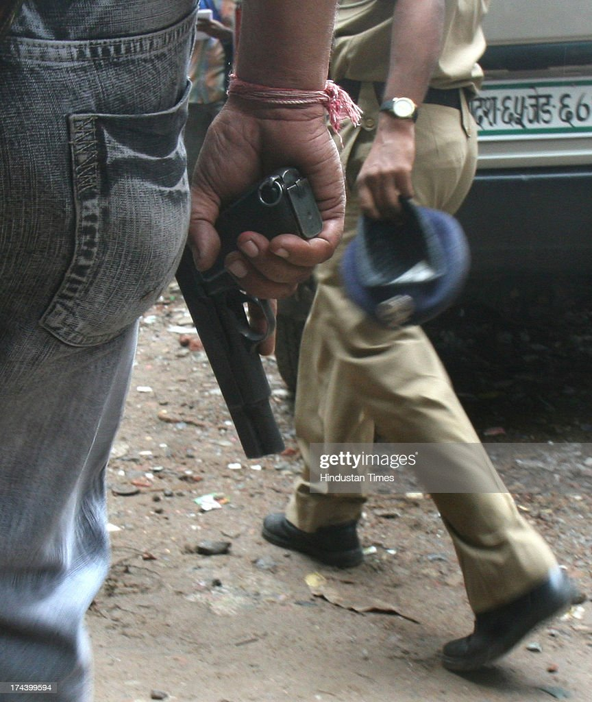 Team of the Delhi Police special cell personnel holding a pistol leaving the encounter spot after the two suspected militants were killed during an encounter, in Jamia Nagar on September 19, 2008 in New Delhi, India. A Delhi court on July 25, 2013 ruled that 2008 Batla House encounter was genuine and convicted lone suspected Indian Mujahideen operative Shahzad Ahmed of killing Delhi police inspector MC Sharma. Shahzad is said to be one of the occupants of the flat in Jamia Nagar where the encounter took place on September 19, 2008 between the officers of the special cell and the suspected IM terrorists allegedly involved in the September 13, 2008 serial blasts at Karol Bagh, Connaught Place, Greater Kailash and India Gate left 26 dead and 133 injured.