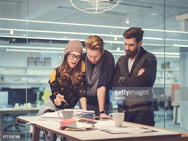 Team of three young people cooperating in the office.