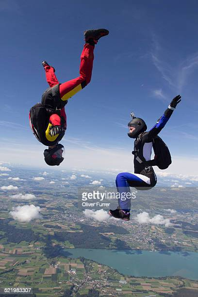 Team of two female skydivers in sit fly and head down positions over Buttwil, Luzern, Switzerland