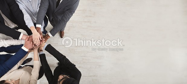 Team of united coworkers standing with hands together : Stock Photo