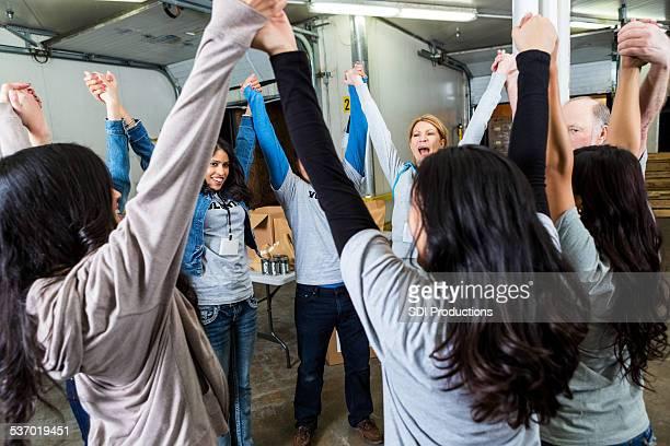 Equipo de voluntarias con las manos en celebración de retención