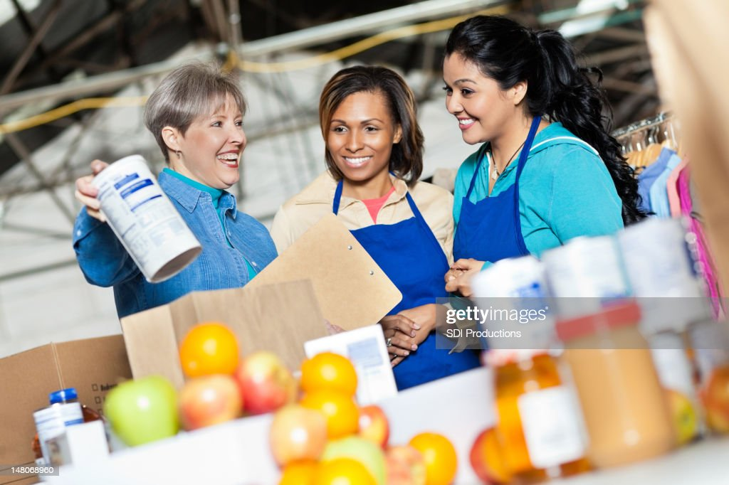Team of volunteers working with donated food at donation center