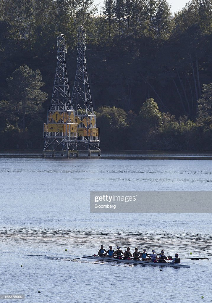 A team of women row past power line crossings on Lake Karapiro, upstream from the Karapiro hydroelectric power station operated by Mighty River Power Ltd., in Karapiro, New Zealand, on Wednesday, May 8, 2013. New Zealand raised NZ$1.7 billion ($1.4 billion) from the sale of Mighty River shares as the nation's biggest initial public offering closed at a price at the lower end of the indicative range. Photographer: Brendon O'Hagan/Bloomberg via Getty Images