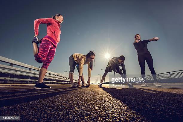 """Équipe de jeunes sportifs s'échauffer sur la route avant de faire de l """" exercice."""